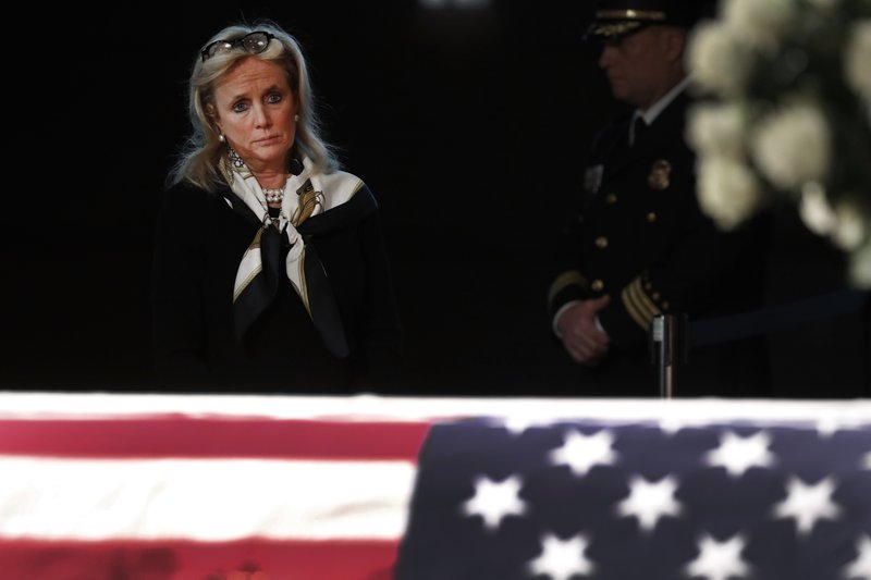 Rep. Debbie Dingell, D-Mich., stands at the casket of her husband and former Rep. John Dingell, lying in repose in Dearborn, Mich. (AP Photo/Paul Sancya)