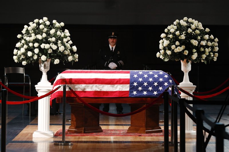 A police officer stands guard stands guard at the casket of former Michigan Rep. John Dingell, lying in repose in Dearborn, Mich. (AP Photo/Paul Sancya)