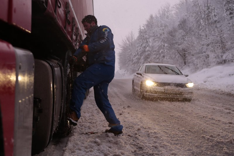 Bosnian truck driver checks tyres on the truck during a snow storm on a road near Sarajevo, Bosnia, Monday, Feb. (AP Photo/Amel Emric)