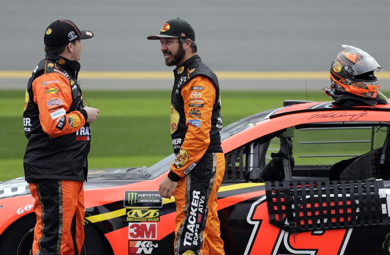 Martin Truex Jr., right, talks with a crew member during a rain delay in the NASCAR Clash auto race at Daytona International Speedway, Sunday, Feb. (AP Photo/Terry Renna)