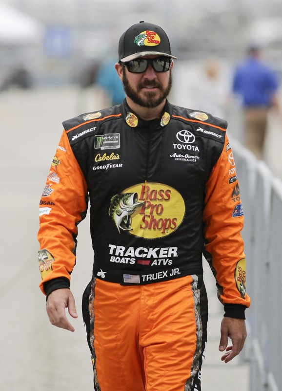Martin Truex Jr. walks down pit road during qualifying for the Daytona 500 auto race at Daytona International Speedway, Sunday, Feb. (AP Photo/Terry Renna)