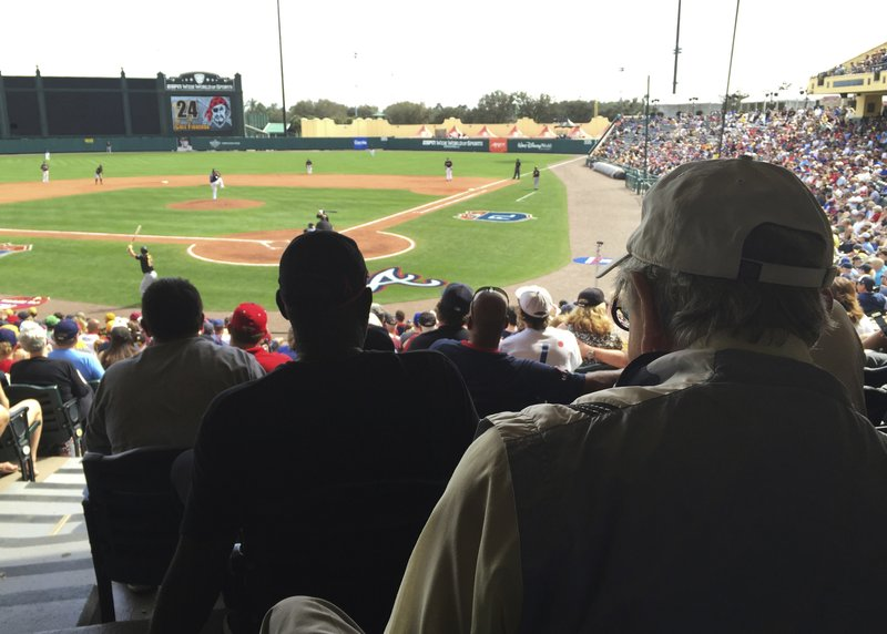 FILE - In this March 5, 2016, file photo, Tommy Giordano, right foreground, special assistant to the general manager of the Atlanta Braves, scouts a spring training baseball game between the Braves and the Pittsburgh Pirates, in Kissimmee, Fla. (AP Photo/Paul Newberry, File)