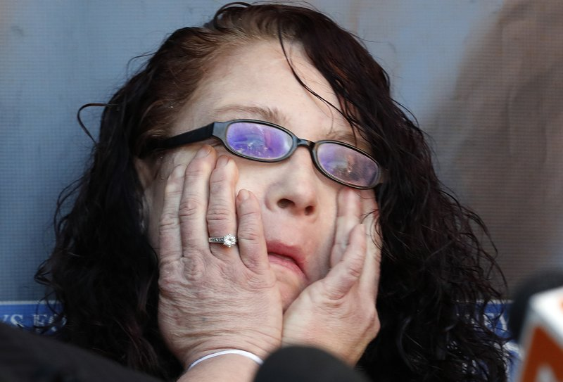 Anya Chapman wipes away tears as attorney Marc J. Victor speaks to the media concerning Chapman's husband, Johnny Wheatcroft, Monday, Feb. (AP Photo/Matt York)
