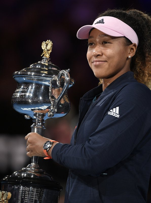 File-This Jan. 26, 2019, file photo shows Japan's Naomi Osaka posing with her trophy after defeating Petra Kvitova of the Czech Republic in the women's singles final at the Australian Open tennis championships in Melbourne, Australia. (AP Photo/Andy Brownbill, File)