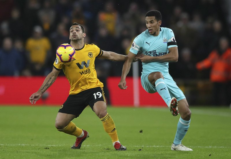 Wolverhampton Wanderers' Jonny Castro, left and Newcastle United's Isaac Hayden battle for the ball, during the English Premier League soccer match between Wolverhampton Wanderers and Newcastle United, at Molineux, in Wolverhampton, England, Monday, Feb. (Nick Potts/PA  via AP)