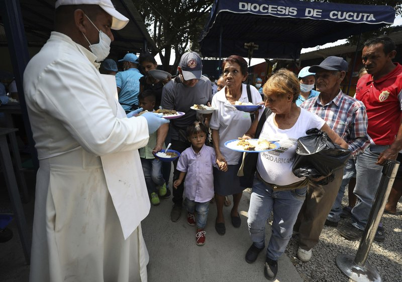 Priest Richard Garcia  hands out free lunches to Venezuelan migrants at the