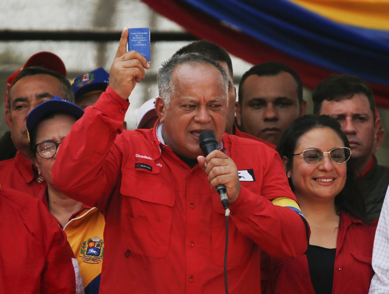 Diosdado Cabello, president of Constitutional Assembly, holds up a miniature copy of the Venezuelan Constitution, during a rally in Urena, Venezuela, Monday, Feb. (AP Photo/Fernando Llano)