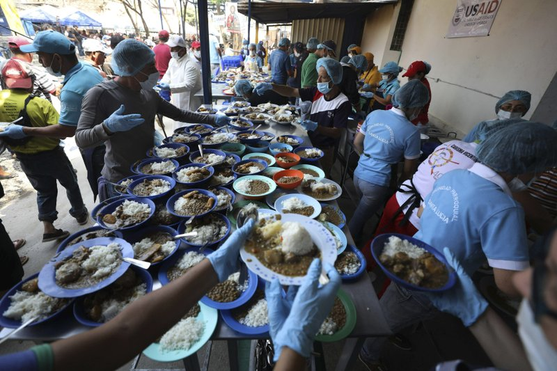 Volunteers prepare free lunches for Venezuelan migrants at the