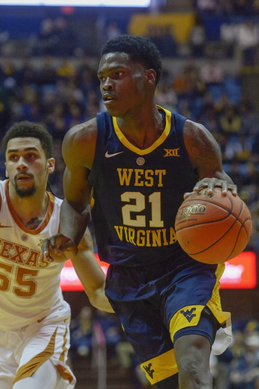 West Virginia forward Wesley Harris (21) drives downcourt during the second half of an NCAA college basketball game against Texas in Morgantown, W. (AP Photo/Craig Hudson)