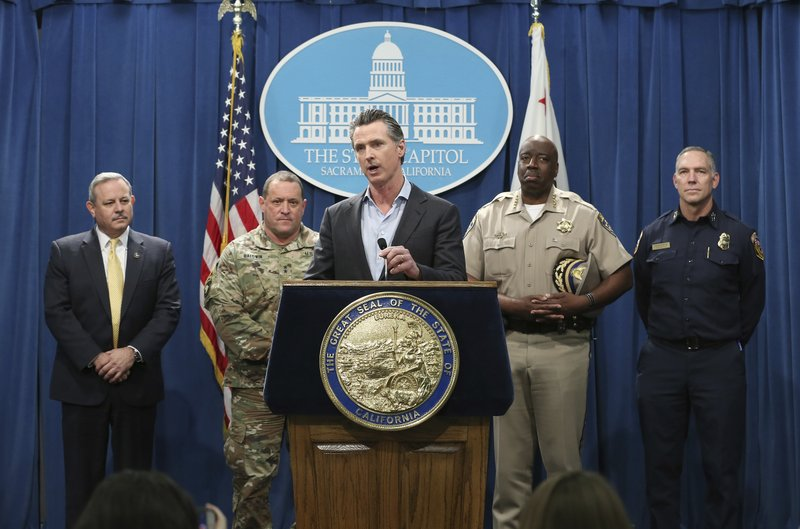 California Gov. Gavin Newsom, center, discusses his decision to withdraw several hundred National Guard troops from the nation's southern border and changing their mission, during a Capitol news conference Monday, Feb. (AP Photo/Rich Pedroncelli)