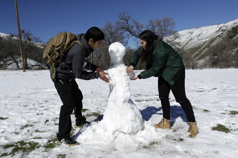 Michael Monsivais, left, makes a snow man with the help of his girlfriend Torrie Martinez at Fort Tejon State Historic Park, Monday, Feb. (AP Photo/Marcio Jose Sanchez)