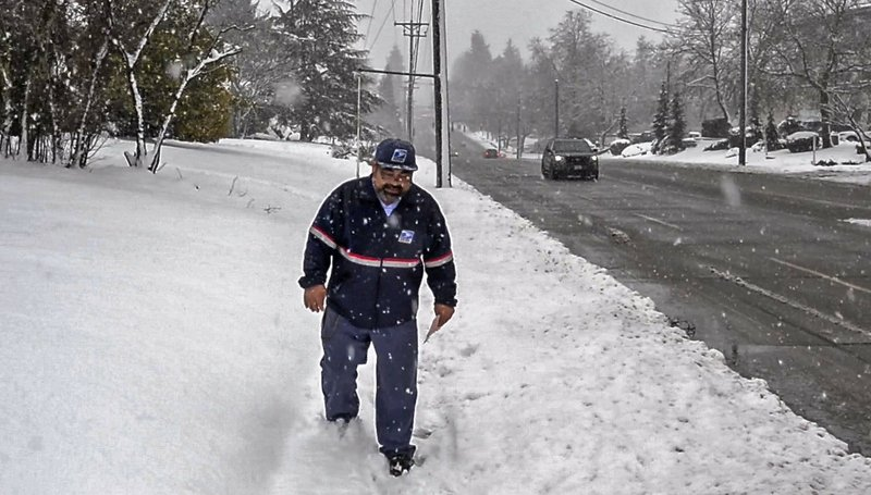 Postal carrier Tom Arndt delivers letters to homes along South 19th Street in Tacoma, Wash., Monday, Feb. (Peter Haley/The News Tribune via AP)