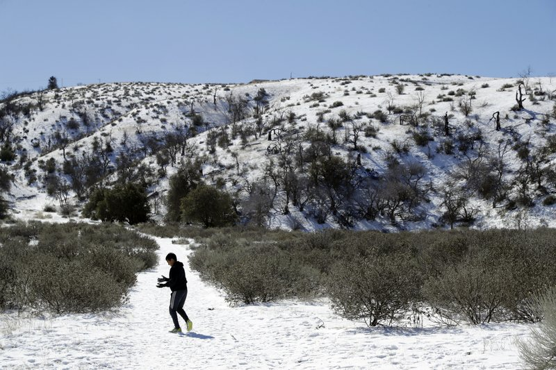 A young visitor walks along a snow covered trail Monday, Feb. 11, 2019, near Lebec, Calif. A series of winter storms socked the U. (AP Photo/Marcio Jose Sanchez)