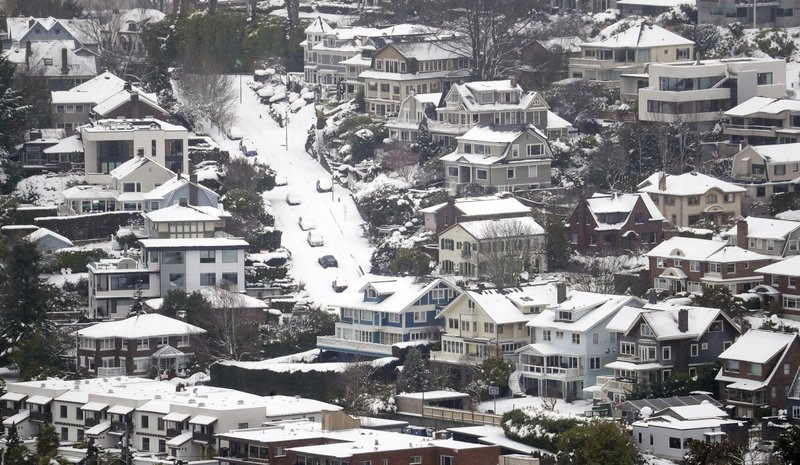 Streets, homes and cars remain snow-covered on one of Seattle's steeper hills, Queen Anne, Monday, Feb. (AP Photo/Elaine Thompson)