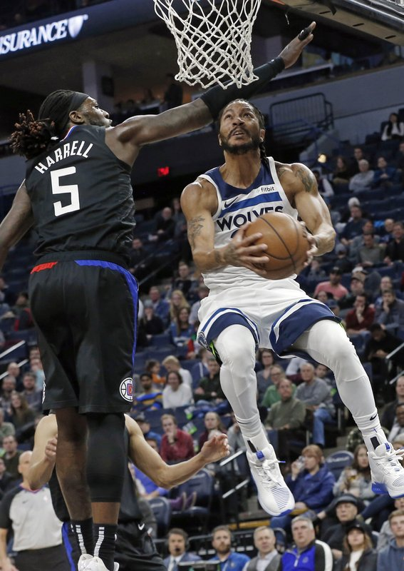 Minnesota Timberwolves' Derrick Rose, right, eyes the basket on a layup as Los Angeles Clippers' Montrezl Harrell defends in the first half of an NBA basketball game Monday, Feb. (AP Photo/Jim Mone)
