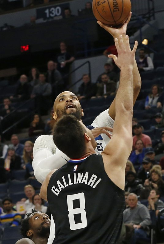 Minnesota Timberwolves' Taj Gibson, top, lays up over Los Angeles Clippers' Danilo Gallinari in the first half of an NBA basketball game Monday, Feb. (AP Photo/Jim Mone)