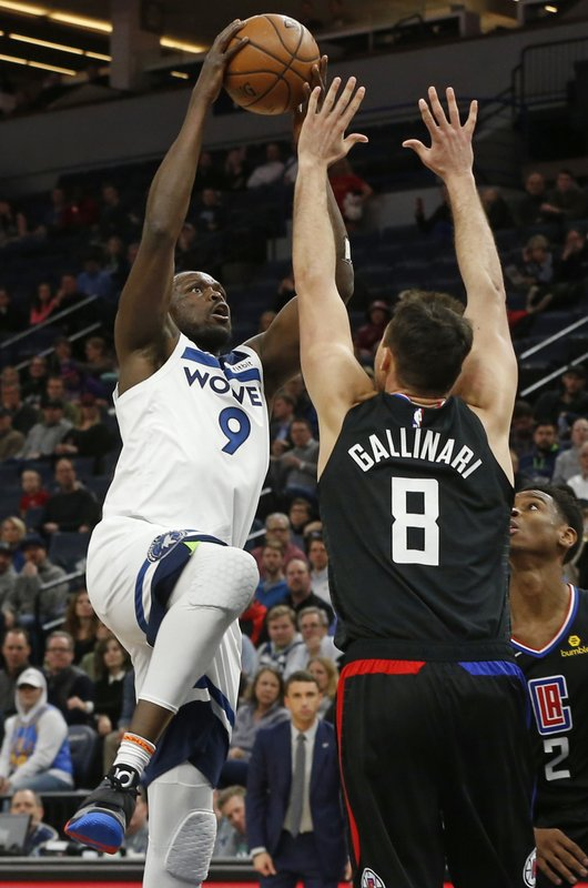 Minnesota Timberwolves' Luol Deng, left, lays up over Los Angeles Clippers' Danilo Gallinari in the first half of an NBA basketball game Monday, Feb. (AP Photo/Jim Mone)