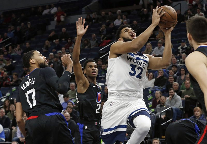 Minnesota Timberwolves' Karl-Anthony Towns, right, lays up as Los Angeles Clippers' Garrett Temple watches in the first half of an NBA basketball game Monday, Feb. (AP Photo/Jim Mone)