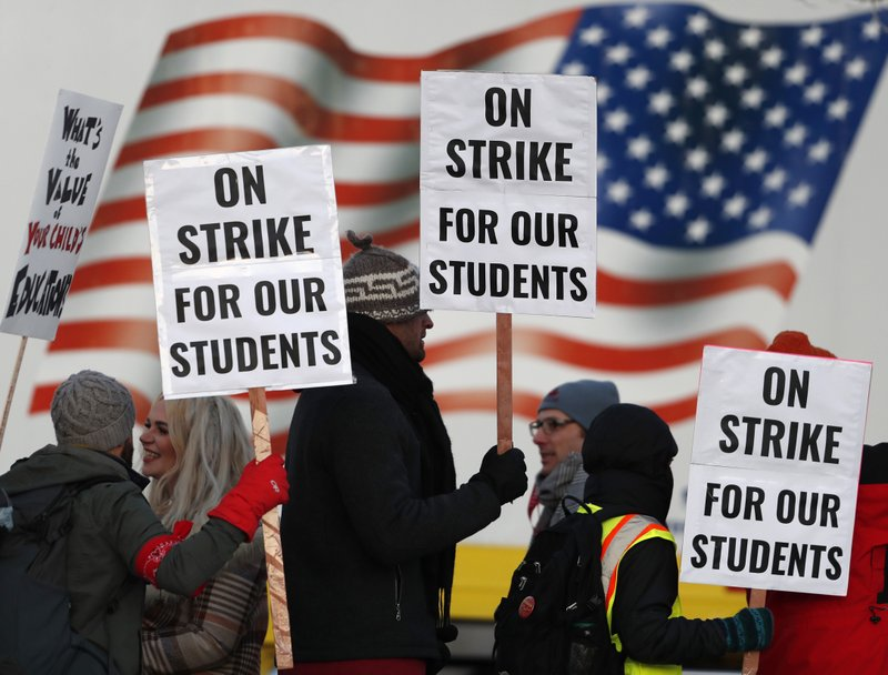 Teachers carry placards as they walk a picket line outside South High School early Monday, Feb. 11, 2019, in Denver. (AP Photo/David Zalubowski)