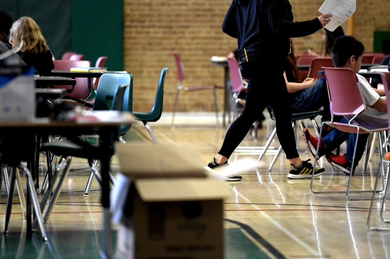 A teacher moves from table-to-table while teaching one of two combined sixth-grade classes in the gymnasium at Skinner Middle School during the first day of the Denver Public Schools teachers strike, Monday, Feb. (Joe Amon/The Denver Post via AP)