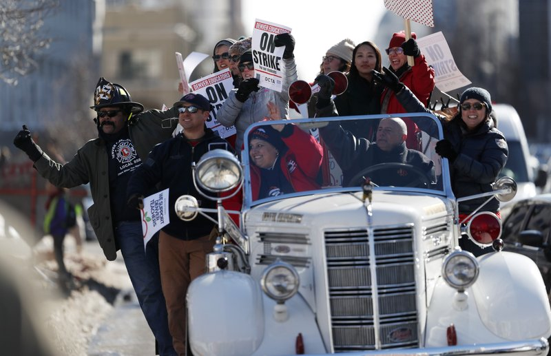 Denver teachers ride on the back of a vintage Denver Fire Department truck past a strike rally on the west steps of the State Capitol Monday, Feb. (AP Photo/David Zalubowski)