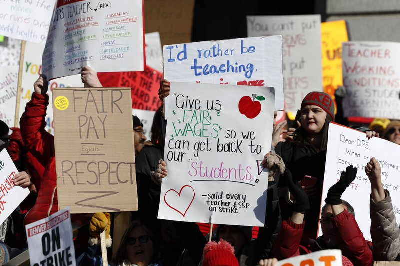 Teachers wave placards during a strike rally on the west steps of the State Capitol Monday, Feb. 11, 2019, in Denver. (AP Photo/David Zalubowski)