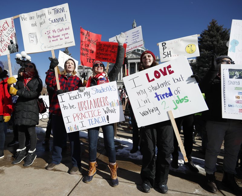 From left, Caitlin Weber, Abby Kloberdanz ad Chelsea Geier, all teachers at Bear Valley International School, wave placards during a strike rally on the west steps of the state Capitol, Monday, Feb. (AP Photo/David Zalubowski)