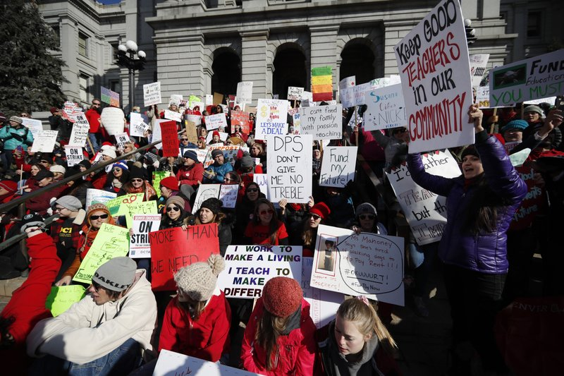 Teachers wave placards during a strike rally on the west steps of the state Capitol, Monday, Feb. 11, 2019, in Denver. (AP Photo/David Zalubowski)