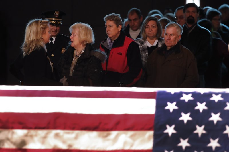Rep. Debbie Dingell, D-Mich., left, greets the public at the casket of her husband, former Rep. John Dingell, lying in repose in Dearborn, Mich. (AP Photo/Paul Sancya)