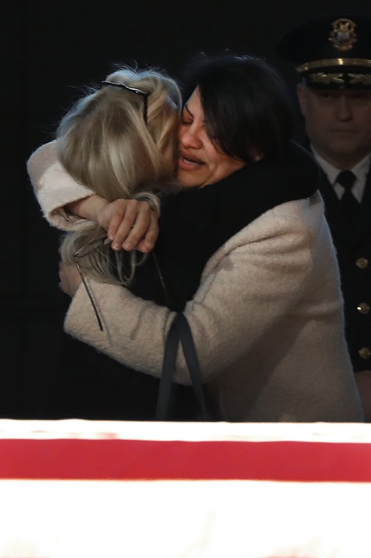 Rep. Debbie Dingell, D-Mich., left, hugs Rep. Rashida Tlaib, D-Mich., at the casket of her husband and former Rep. (AP Photo/Paul Sancya)