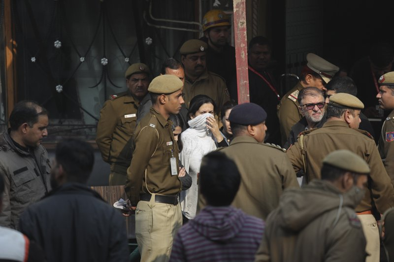 Policemen and others stand at the spot after an early morning fire at the Arpit Palace Hotel killed more than a dozen people in the Karol Bagh neighborhood of New Delhi, India, Tuesday, Feb. (AP Photo/Manish Swarup)