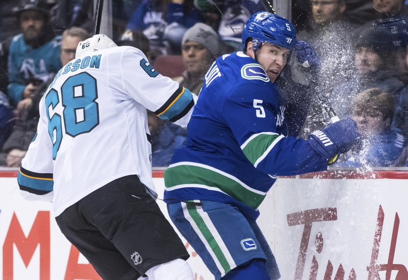 San Jose Sharks' Melker Karlsson, left, of Sweden, checks Vancouver Canucks' Derrick Pouliot during the first period of an NHL hockey game in Vancouver, British Columbia, on Monday, Feb. (Darryl Dyck/The Canadian Press via AP)