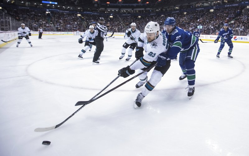 San Jose Sharks' Barclay Goodrow (23) is checked by Vancouver Canucks' Ben Hutton (27) during the first period of an NHL hockey game in Vancouver, British Columbia, on Monday, Feb. (Darryl Dyck/The Canadian Press via AP)