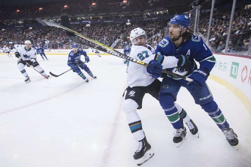San Jose Sharks' Joonas Donskoi (27), of Finland, and Vancouver Canucks' Chris Tanev collide during the first period of an NHL hockey game in Vancouver, British Columbia, on Monday, Feb. (Darryl Dyck/The Canadian Press via AP)
