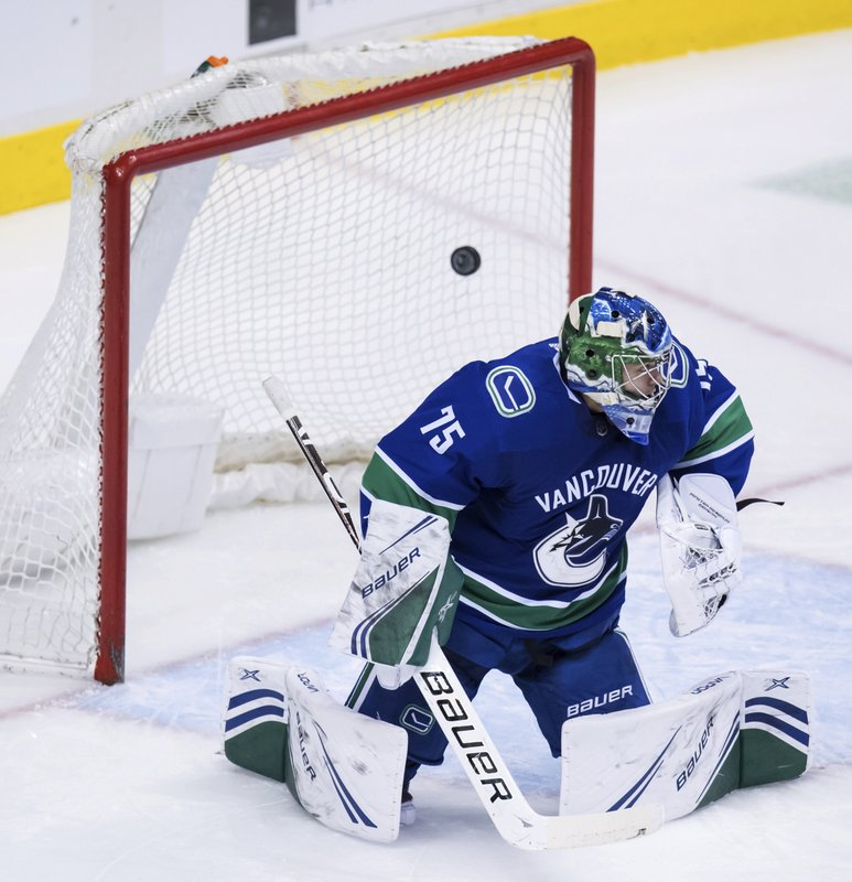 Vancouver Canucks goalie Michael DiPietro allows a goal to San Jose Sharks' Evander Kane, not seen, during the second period of an NHL hockey game in Vancouver, British Columbia, on Monday, Feb. (Darryl Dyck/The Canadian Press via AP)