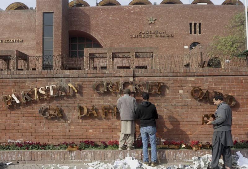 In this Feb. 10, 2019, photo, Pakistani staff fix the name of Gadaffi stadium in preparation for the upcoming Pakistan Super League in Lahore, Pakistan. (AP Photo/K.M. Chaudary)