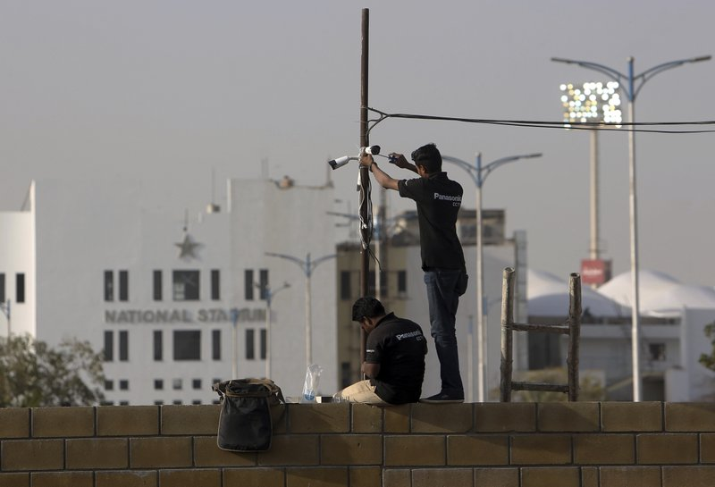 In this Feb. 9, 2019, photo, Pakistani technician fix security cameras at National Stadium ahead of upcoming Pakistan Super League in Karachi, Pakistan. (AP Photo/Fareed Khan)