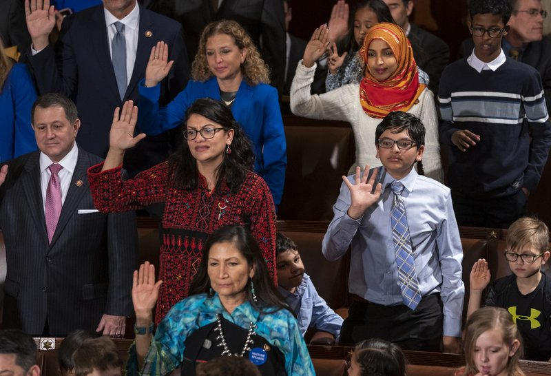 FILE - In this Jan. 3, 2019 file photo, Rep. Rashida Tlaib, D-Mich., center left, wears a Palestinian thobe as Democratic members of the House of Representatives take their oath on the opening day of the 116th Congress, at the Capitol in Washington. (AP Photo/J. Scott Applewhite, File)