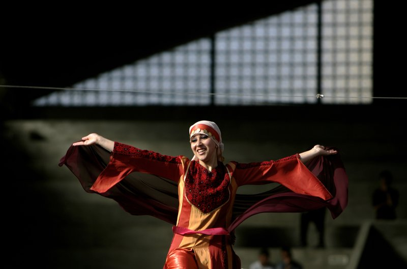 FILE - In this April 29, 2007 file photo, a Palestinian woman wearing a Palestinian dress with traditional embroidery performs a folk dance known as Debka, during a folk festival in the West Bank city of Ramallah. (AP Photo/Muhammed Muheisen, File)