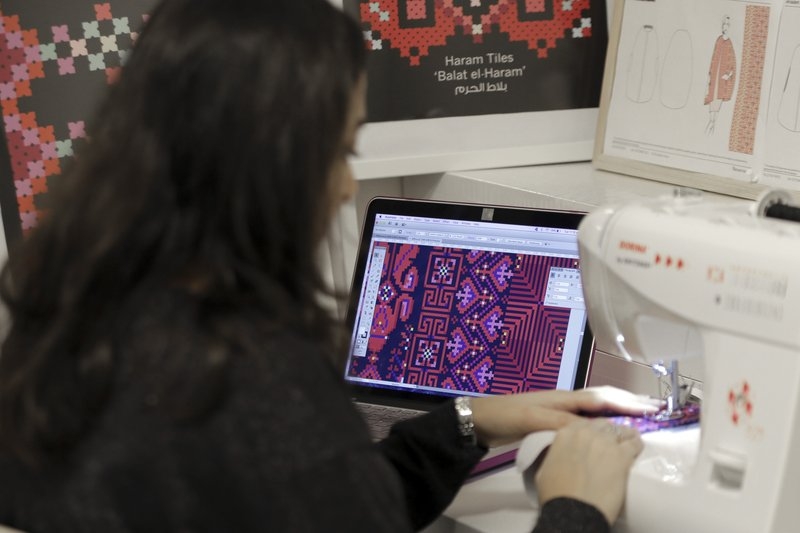 In this Tuesday, Jan. 29, 2019 photo, designer Natalie Tahhan works in her studio in east Jerusalem. The thobe, a brightly embroidered robe for women, has long been a staple of Palestinian life, sewn by village women and worn at weddings and parties. (AP Photo/Mahmoud Illean)