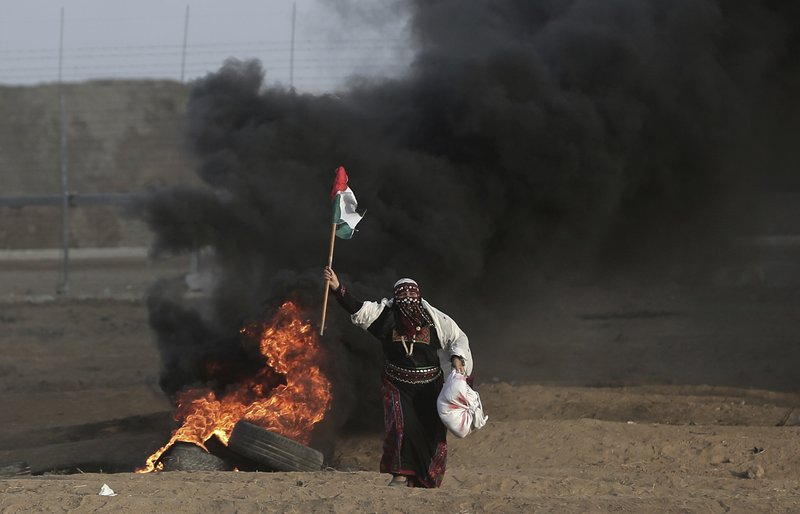 FILE - In this Oct. 5, 2018 file photo, a Palestinian woman wearing a traditional thobe, carries a Palestinian flag during a protest at the Gaza Strip's border with Israel. (AP Photo/Khalil Hamra, File)