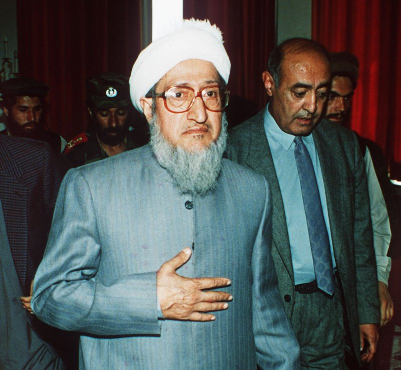 FILE - In this April 29, 1992, file photo, then Afghan President Sibghatullah Mujadidi leaves the Foreign Ministry in Kabul, Afghanistan, after briefing foreign diplomats on his first full day in power. (AP Photo/Udo Weitz, File)