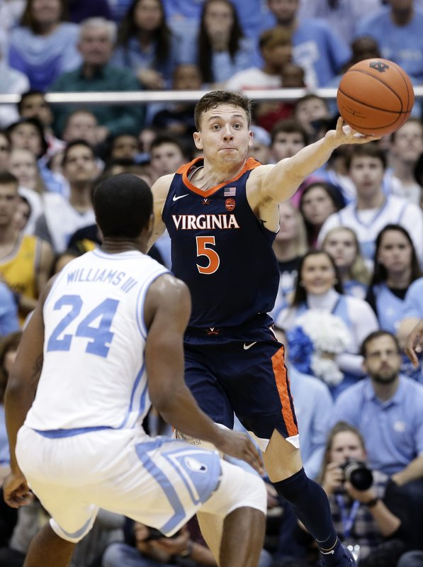 North Carolina's Kenny Williams (24) guards Virginia's Kyle Guy (5) during the second half of an NCAA college basketball game in Chapel Hill, N. (AP Photo/Gerry Broome)