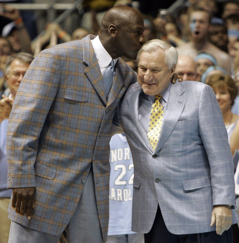 File-This Feb. 10, 2007, file photo shows former North Carolina player Michael Jordan, left, giving his former coach Dean Smith a kiss during halftime of a college basketball game between North Carolina and Wake Forest in Chapel Hill, N. (AP Photo/Gerry Broome, File)