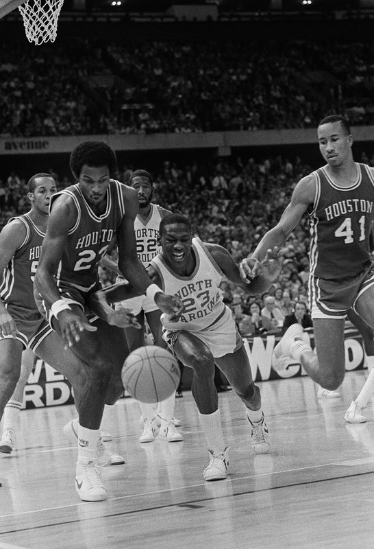 File- This March 29, 1982, file photo shows Houston's Clyde Drexler, left, and North Carolina's Michael Jordan, center, battling for the ball  during NCAA semifinal final game in New Orleans. (AP Photo/ File)