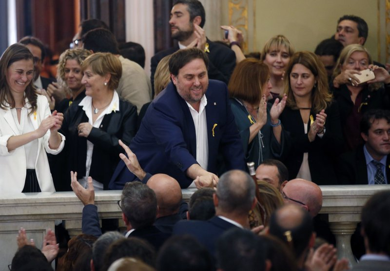 FILE - In this Friday, Oct. 27, 2017 file photo, Catalan Vice President Oriol Junqueras, center, is greeted after a vote on independence in the Catalan parliament in Barcelona, Spain. (AP Photo/Manu Fernandez, File)