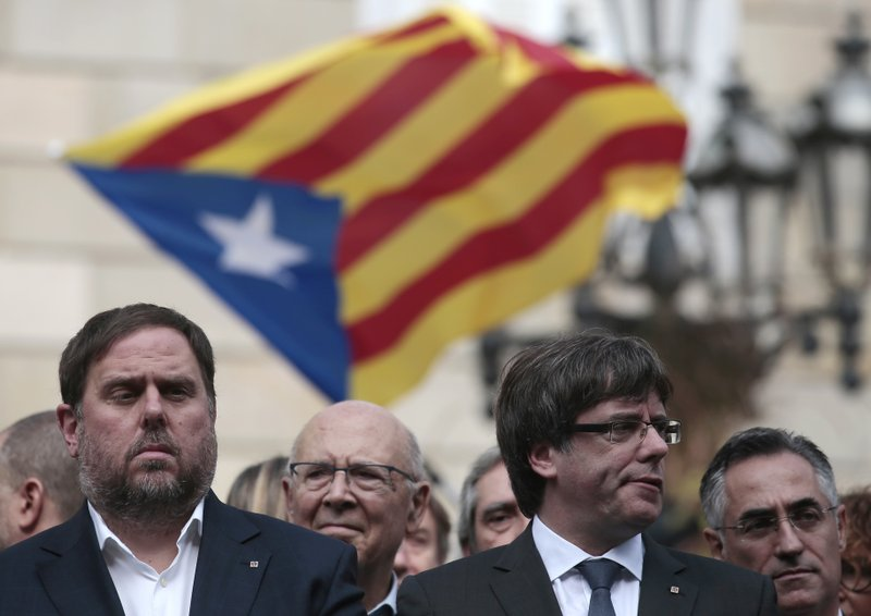 FILE - In this Monday, Oct. 2, 2017 file photo, Catalan regional Vice-President, Oriol Junqueras, left, and Catalan President, Carles Puigdemont, attend a protest called by pro-independence supporters outside the Palau Generalitat in Barcelona, Spain. (AP Photo/Manu Fernandez, File)