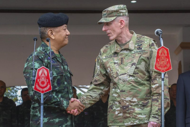 In this photo by release Royal Thai Armed Forced Headquarters, The Royal Thai Armed Forces, Gen. Pornpipat Benyasri, left shakes hands with Commander, U. (Royal Thai Armed Forced Headquarters via AP)
