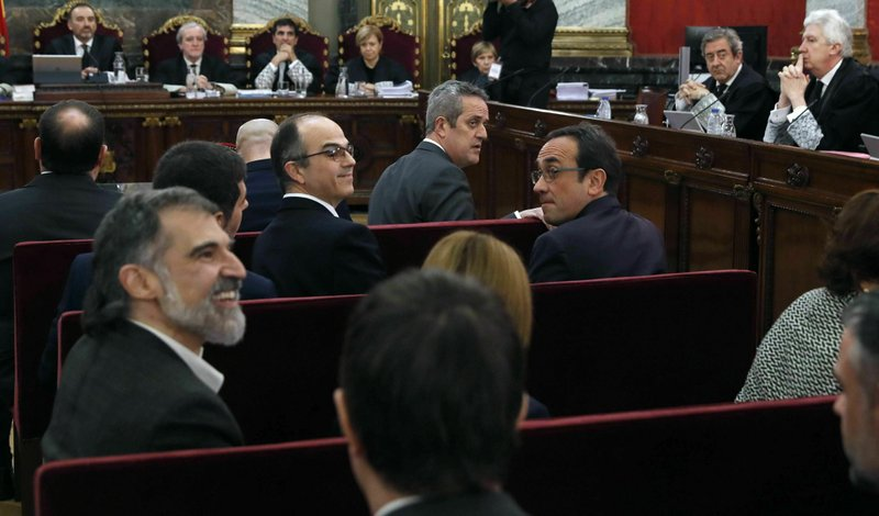 Jordi Cuixart, president of the Catalan Omnium Cultural organization, left, sits next to other eleven separatist leaders during the trial at the Spanish Supreme Court in Madrid, Tuesday, Feb. (J.J. Guillen/Pool via AP)