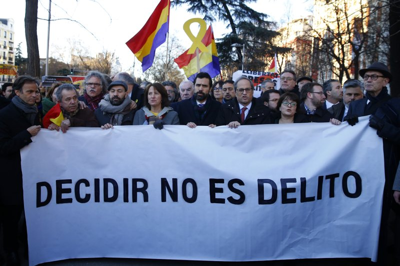 The president of Catalonian Parliament, Roger Torrent, center, and the Catalan regional President Quim Torra, center right, hold a placard that reads in Spanish:
